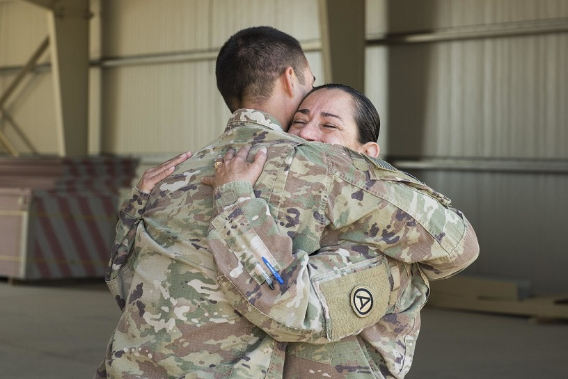 two military personnel hugging
