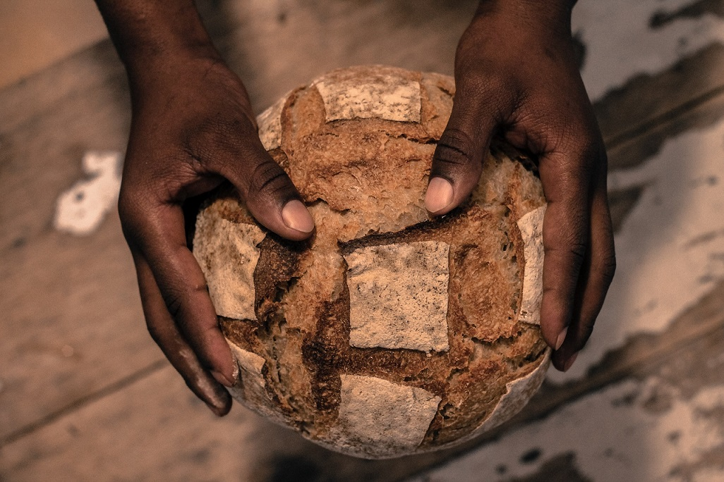 photo of hands holding bread