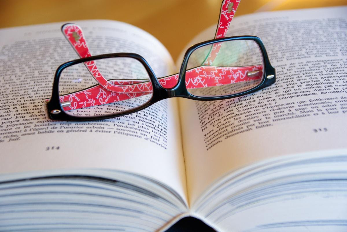 photo of reading glasses lying on top of book