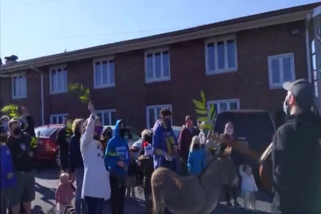 photo of parishioners with donkey outside of the church