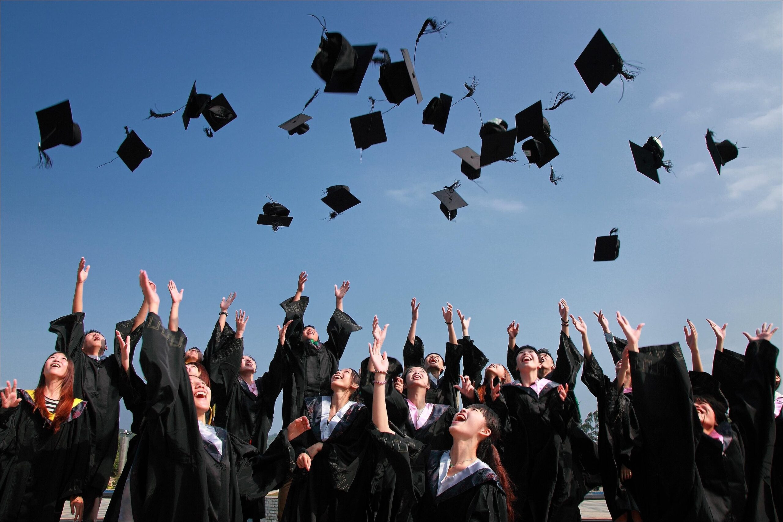 photo of graduates throwing caps into the air