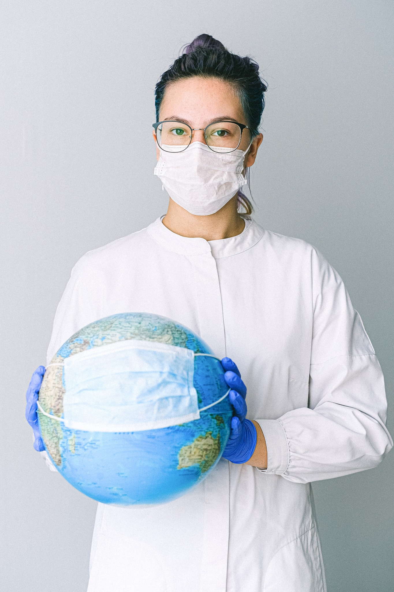 healthcare worker who is masked holding a globe with a mask on it